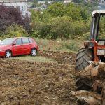 Un tractorista ara una finca dejando coches aparcados en su interior