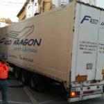 Un camión de Frío Aragón daña fachadas, vehículos y se atasca en el centro de Ablitas