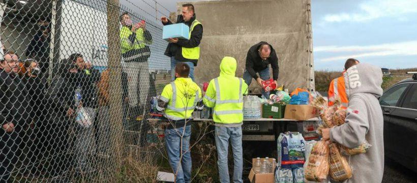 Los voluntarios tienen que entregar víveres a los camioneros por las alambradas, como si fueran presos