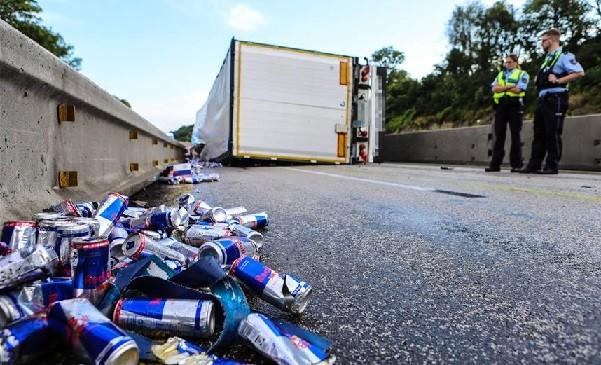 red bull dosen liegen vor einem umgekippten lastwagen auf 2569822